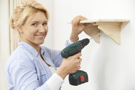 taladro: Mujer que pone encima del estante de madera en el país usando taladro inalámbrico