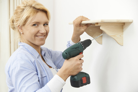 drill: Woman Putting Up Wooden Shelf At Home Using Cordless Drill