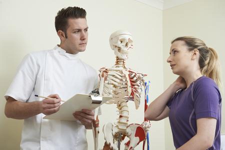 osteopath: Female Patient Describing Neck Injury To Osteopath