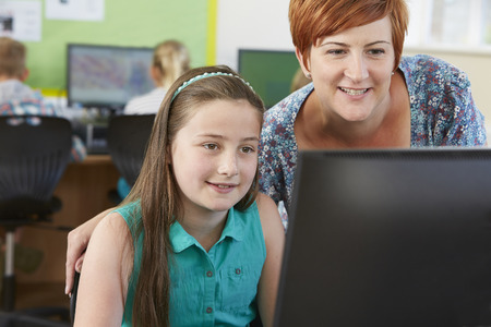 Female Elementary Pupil In Computer Class With Teacher photo
