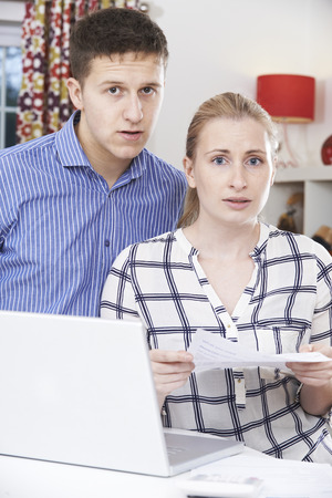 home finances: Worried Couple Discussing Domestic Finances At Home Stock Photo