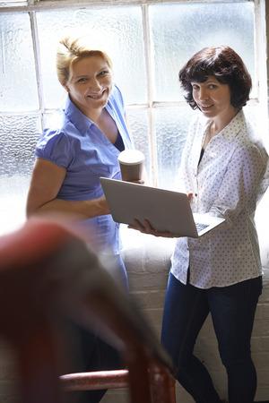 informal: Two Businesswomen With Laptop Having Informal Meeting In Office