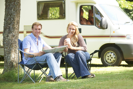 motor home: Couple Relaxing Outside Motor Home On Vacation Stock Photo