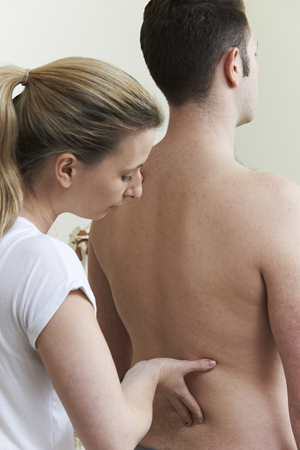 treating: Female Osteopath Treating Male Patient With Back Problem Stock Photo