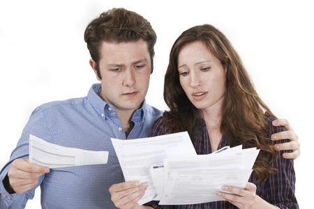 finance problems: Studio Shot Of Worried Couple Looking At Bills