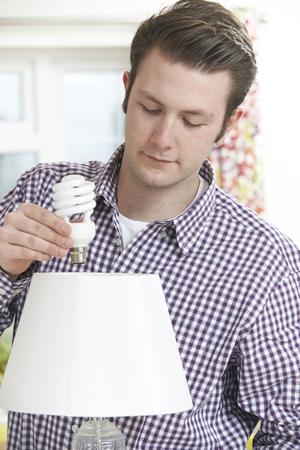 ahorro energia: Hombre que pone la bombilla de baja energía en la lámpara en casa