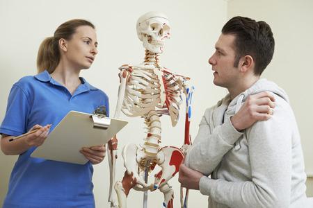 masaje deportivo: Paciente de sexo masculino Describiendo Lesiones Para oste�pata Foto de archivo