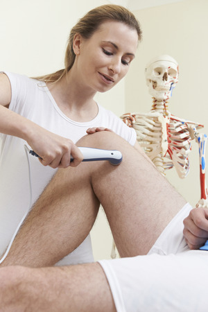 osteopath: Osteopath Giving Ultrasound Treatment To Male Client With Sports Injury Stock Photo