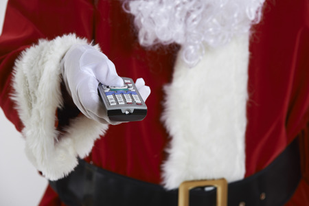 television remote: Close Up Of Santa Claus Holding Television Remote Control