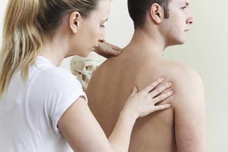 mujeres de espalda: Osteópata femenina, tratamiento de paciente con problema en el hombro Foto de archivo