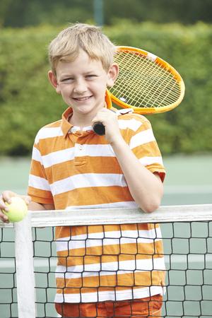 child sport: Portrait Of Boy Playing Tennis Standing Next To Net