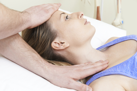 adjustment: Male Osteopath Treating Female Patient With Neck Problem