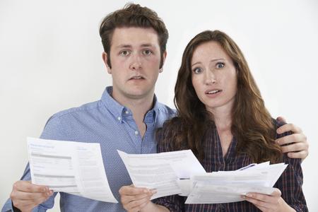 finance background: Studio Shot Of Worried Couple Looking At Bills