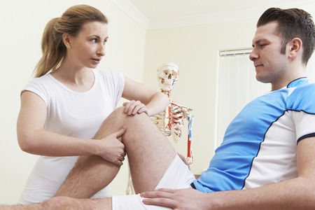 work injury: Osteopath Giving Ultrasound Treatment To Male Client With Sports Injury Stock Photo