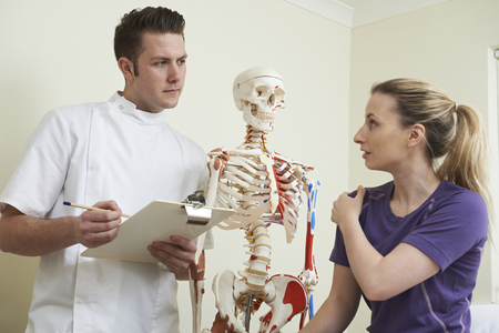 osteopath: Female Patient Describing Shoulder Injury To Osteopath Stock Photo
