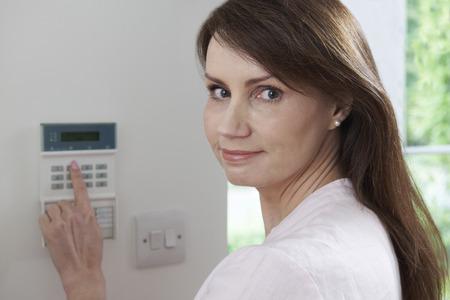 ホーム セキュリティ システムのコントロール パネルの設定の女性