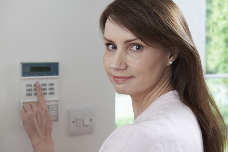 home security system: Woman Setting Control Panel On Home Security System Stock Photo