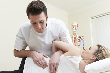 osteopath: Male Osteopath Treating Female Patient With Back Problem