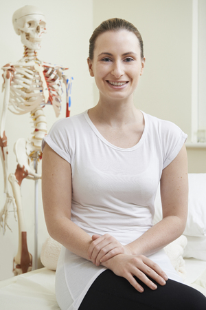 osteopath: Portrait Of Female Osteopath In Consulting Room