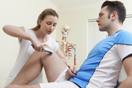 ultrasound: Osteopath Giving Male Client Ultrasound Treatment