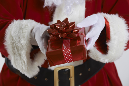 wrapped present: Close Up Of Santa Claus Holding Gift Wrapped Present
