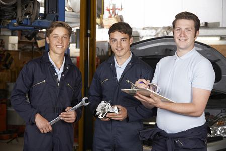 trainees: Mechanic Teaching Trainees In Garage Workshop