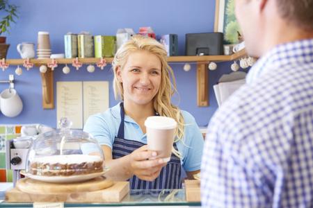 alimentos y bebidas: Camarera En Caf� Sirviendo al Cliente Con Caf� Foto de archivo