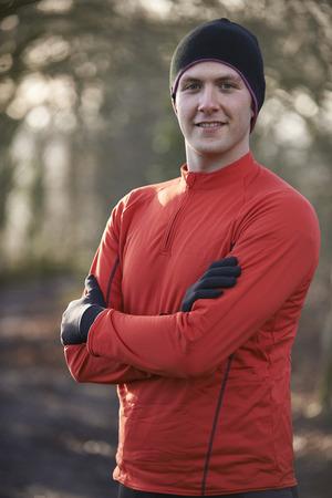 winter escape: Portrait Of Man On Winter Run Through Woodland Stock Photo