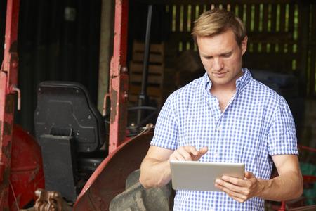 Farmer die digitale tablet die zich in de schuur met ouderwetse tractor