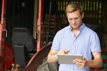 farm equipment: Farmer Holding Digital Tablet Standing In Barn With Old Fashioned Tractor