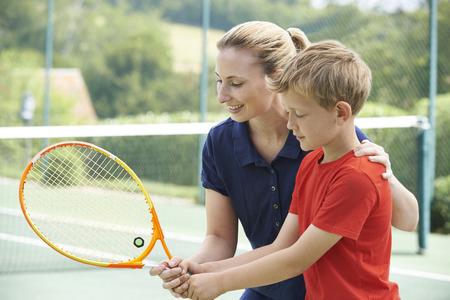 teach: Female Tennis Coach Giving Lesson To Boy