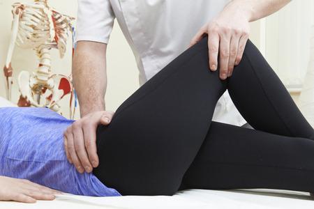 de rodillas: Oste�pata masculina Tratamiento del Paciente femenino con problema de cadera Foto de archivo