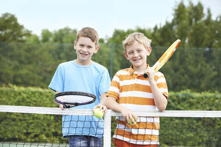 two boys: Portrait Of Two Boys Playing Tennis Together Stock Photo