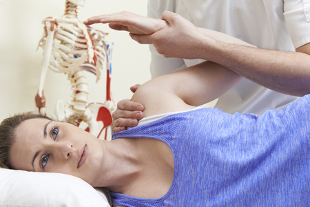 shoulder problem: Male Osteopath Treating Female Patient With Shoulder Problem Stock Photo