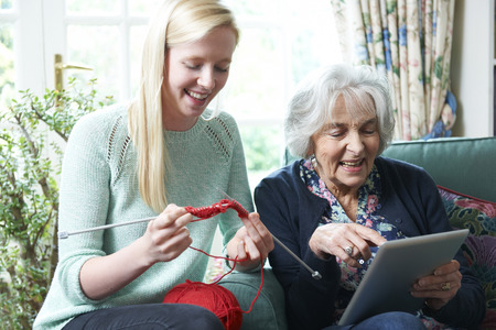 whilst: Grandmother Using Digital Tablet Whilst Granddaughter Knits