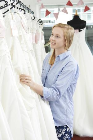business dress: Bride Choosing Dress In Bridal Boutique