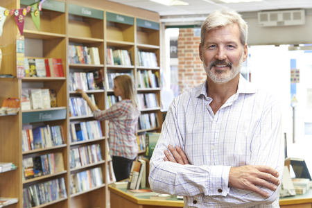 Portrait Of Male Bookstore Owner With Customer In Background