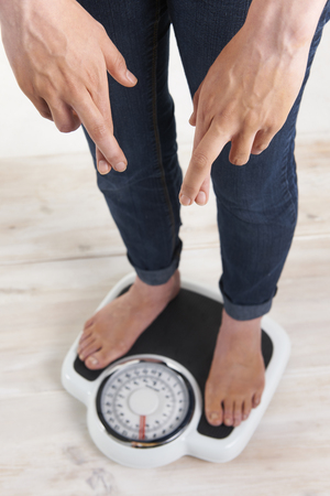 women's issues: Woman Standing On Scales With Fingerrs Crossed