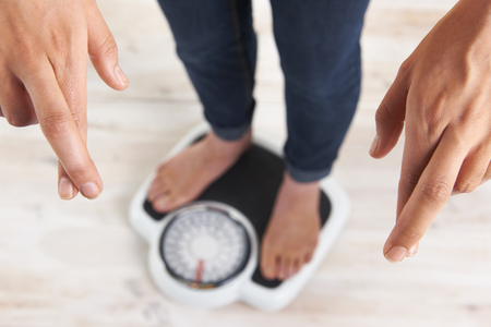women's issues: Woman Standing On Scales With Fingers Crossed