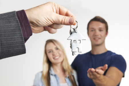 handing over: Estate Agent Handing Over House Keys To Young Couple Stock Photo