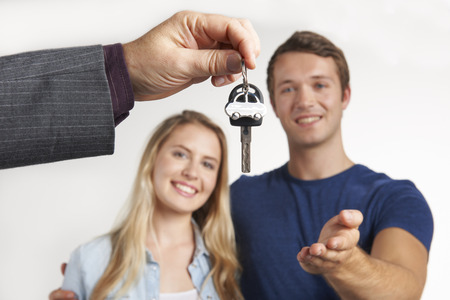 handing over: Dealer Handing Over Keys For New Car To Young Couple
