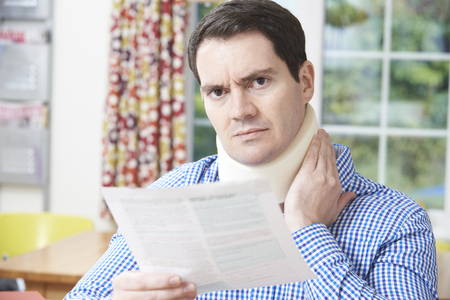 illness: Man Reading Letter After Receiving Neck Injury