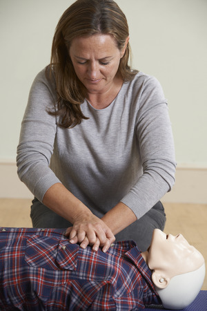 recovery position: Woman Using CPR Technique On Dummy In First Aid Class Stock Photo