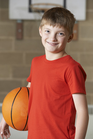 child smile: Portrait Of Boy Holding Basketball In School Gym