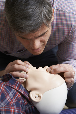safety first: Man In First Aid Class Performing Mouth To Mouth Resuscitation On Dummy