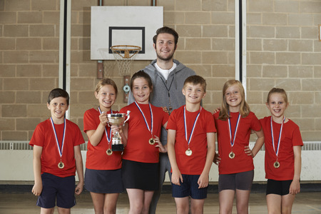 the victorious: Victorious School Sports Team With Medals And Trophy In Gym