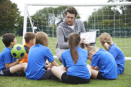 sports: Coach Giving Team Talk To Elementary School Soccer Team