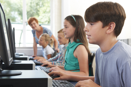 Group Of Elementary Pupils In Computer Class With Teacher Stock Photo