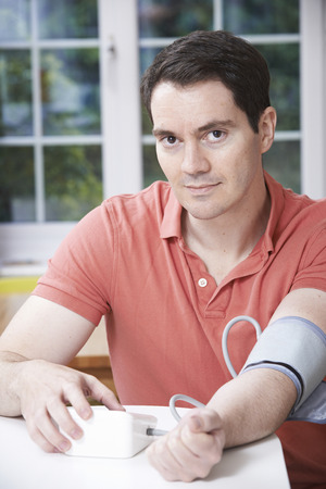 measuring: Man Measuring Blood Pressure At Home