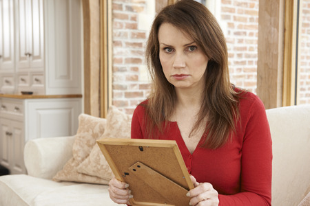 abducted: Unhappy Mature Woman Looking At Photograph In Frame Stock Photo
